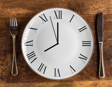 Eight hour feeding window concept or breakfast time with clock on plate and knife and fork on wooden table, overhead view Stock fotó