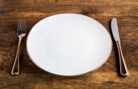 Empty luxurious white plate with knife and fork on wooden table, high angle view