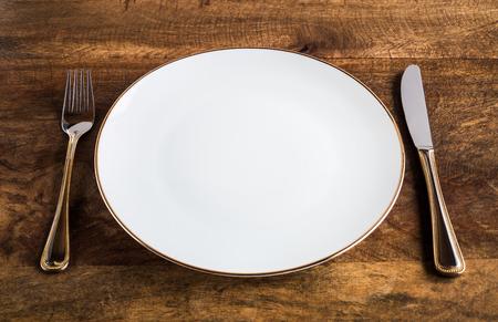 Lege luxueuze witte plaat met mes en vork op houten lijst, hoge hoekmening Stockfoto