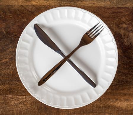 Intermitterend vastend concept met mes en vork die dwarssymbool op witte plaat tegen houten lijst, hoogste mening tonen Stockfoto