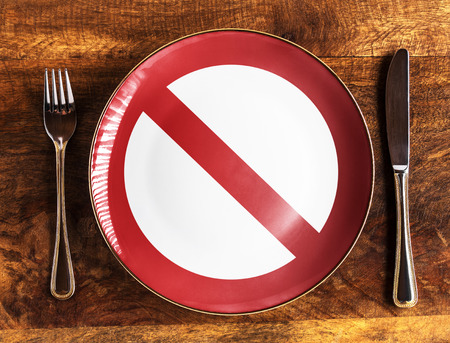 No food concept with forbidden symbol on plate with fork and knife on wooden table, overhead view