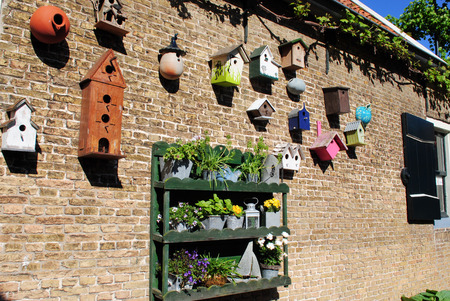 Several different shaped an colored bird houses on a brick wall photo