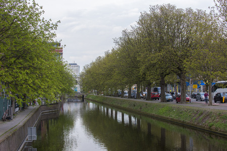 cycler: Town Canal on Kortenaerkade in the Hague, Den Haag, the Netherlands on with a group of Horse Chestnuts (Aesculus hippocastanum) on both sides Stock Photo