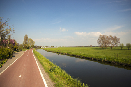 polder: Cycle Path and Canal through a Dutch Polder Landscape in Maasland, the Netherlands Stock Photo