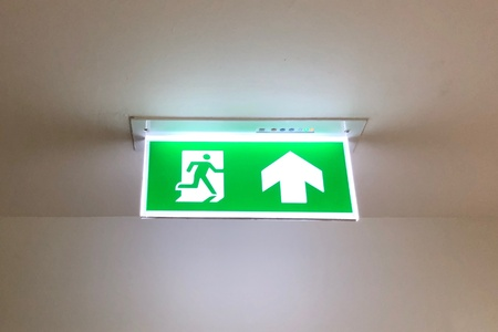Glowing emergency exit sign hanging on the ceiling