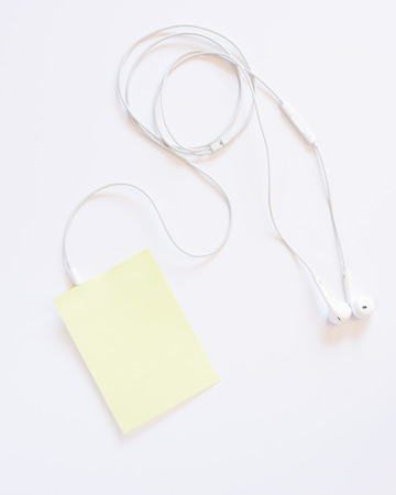 Headphones and a sticky note with blank text space