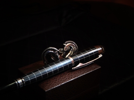 precious pen and cuff link in dark  photo