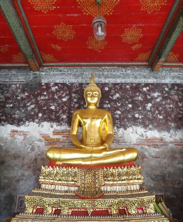 front view statue of golden Buddha with ancient painting wall