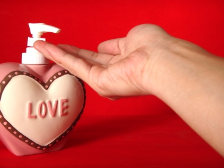 action of hand receiving the hand cleanser gel from the heart shape of bottle with letter  Love   on it and red background