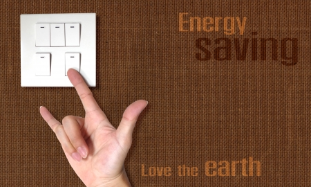 energy saving theme the act of hand in symbol of love switch off the light on the wood board wall