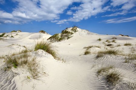 Blues sky with clouds over sandy dunes