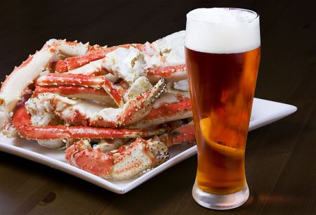 crab: Plate with a pile of crab legs and a glass of amber beer (clipping paths are included)