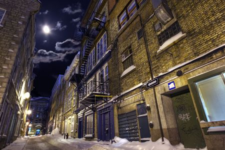 winter escape: Empty street in a winter night highlighted by moon Stock Photo