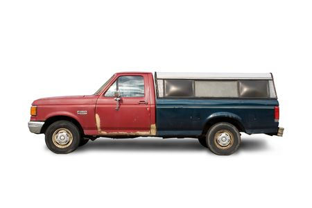 Old truck that badly needs body repairs on white background