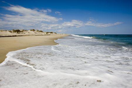 Ocean Wellen Uberschlag zum verlassen weißen Schaum, der in der Sonnenlicht funkelt Horizont Strand Dehnung.