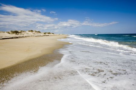 Ocean waves roll over stretching to the horizon beach leaving white foam that sparkles in the sun light. Standard-Bild