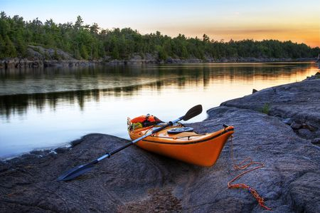 Orange kayak left on a rocky river bank with the sunset skies on the background