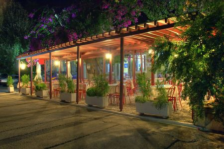Deserted restaurant highlighted by electrical light surrounded by plants and flowers in the middle of a Summer night