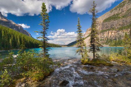 Ein Strom fließt in einen Bergsee. Moraine Lake, Banff, AB, Kanada Lizenzfreie Bilder