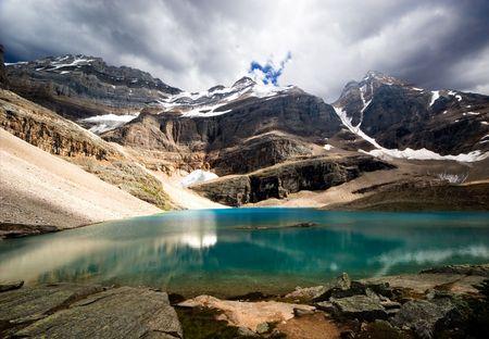 A mountain lake highlighted by sun Standard-Bild