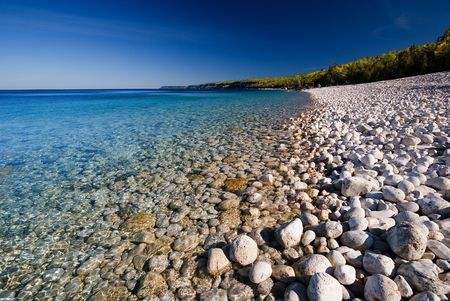 White pebble beach and crystal clear lake.
