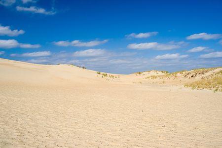 Blues Himmel mit weißen Wolken über Sand