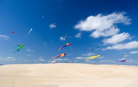 Multicolor kites flying over sandy hill in bright sunny afternoon Standard-Bild