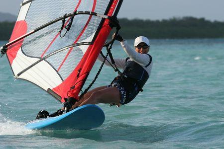 Eine junge Frau pauschal über einen blauen Lagune auf einem Windsurfer
