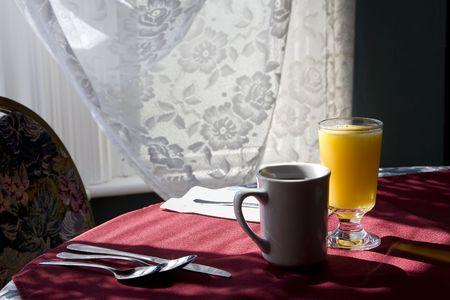 Glass of orange juice and cap of coffee on a table chair highlighted by the sunlight from  the window. Standard-Bild