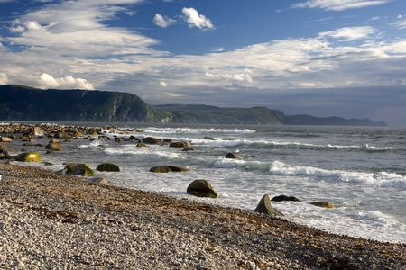 Waves highlighted by late afternoon sun break on a pebble beach Standard-Bild