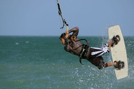 Kitesurfer performing a jump covered with a splash of water drops