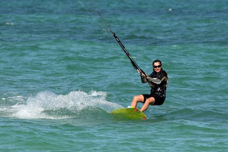 Young pretty woman riding a kite