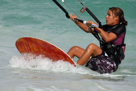Young pretty girl in a wetsuit learns to kitesurf Standard-Bild