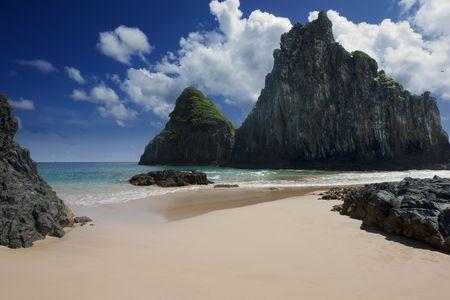 Sandy beach surrounded by rocks taken against deep blue skies covered with few clouds. Picture is taken on Fernando de Noronha Island, Brazil. Standard-Bild