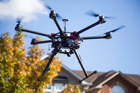 A flying hexacopter with spinning propellers and without a camera with some out of focus skies trees and houses on the background Standard-Bild