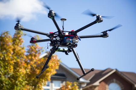 Ein fliegender Hexacopter mit Spinn Propeller und ohne Kamera mit etwas unscharf Himmel Bäume und Häuser auf dem Hintergrund Lizenzfreie Bilder