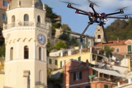 A flying drone without a camera with a blured old town in the background