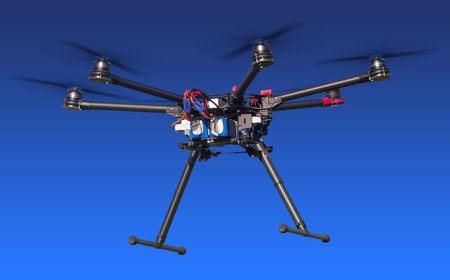 A flying hexacopter with a blue background. Includes clipping path