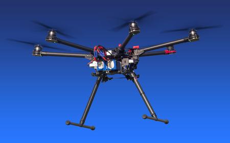Ein fliegender Hexacopter mit einem blauen Hintergrund. Einschließlich Beschneidungspfad Lizenzfreie Bilder