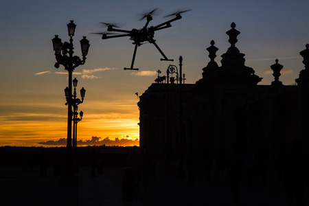 A silhouette of a flying drone with a dramatic sunset and elements of European architecture in the background. Standard-Bild