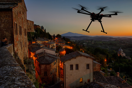 A silhouette of a flying drone with a dramatic sunset in the background in the skies of old European city Standard-Bild