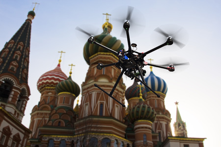 A flying hexacopter without a camera shot from below with the blue skies and blured features of Red Square in the background