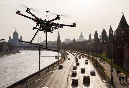 camera: A flying hexacopter without a camera shot from a side with the a blured silhouette of Moscow in the background Stock Photo