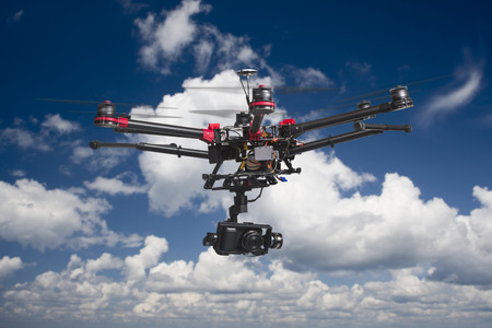 Ein fliegender Multicopter mit erhobenen Fahrwerke und eine Kamera in schönen bewölktem Himmel