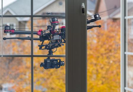 Eine Drohne mit einer Kamera hinter einem offenen Schlafzimmerfenster fliegen. Lizenzfreie Bilder