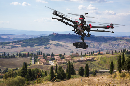 drone: A flying helicopter with raised landing gears and a camera with blured hills of Tuscany in the background