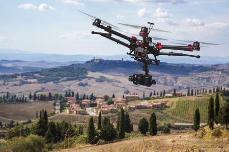 Ein fliegender Hubschrauber mit erhobenen Fahrwerke und eine Kamera mit blured Hügeln der Toskana im Hintergrund