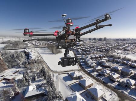 Eine Drohne mit einer Kamera und hob Fahrwerke hoch über einem Wohngebiet mit frischem Schnee in einem hellen, sonnigen Wintertag fliegen. Lizenzfreie Bilder
