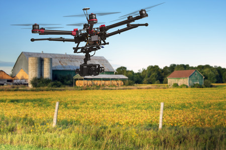 A flying helicopter with raised landing gears and a camera with blurred crop field and farm structures on a background highlighted by a sunset Standard-Bild