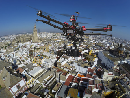 city surveillance: An aerial view of a flying multi-copter with raised landing gears and a camera with slightly blured center of old Seville in the background Stock Photo